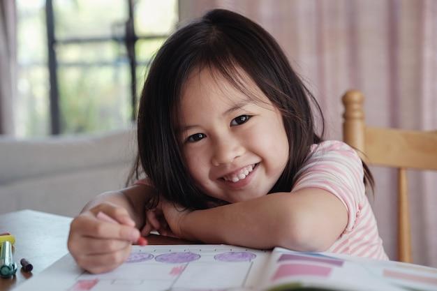 若いアジア人の女の子、家庭で描く、ホームスクールの教育