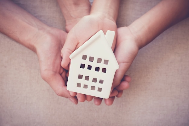 白い家、家族の家、ホームレスの避難所のコンセプトを保持している大人と子供の手