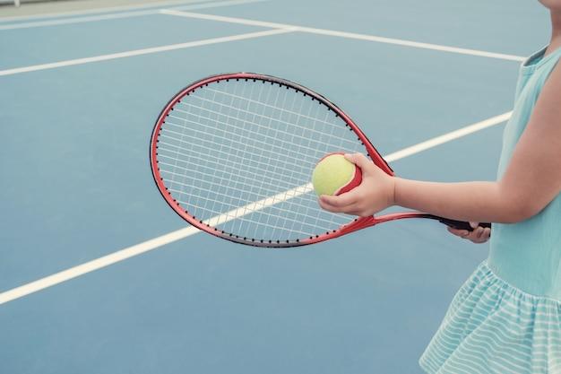 屋外の青いコートで若いアジアの女の子のテニス選手