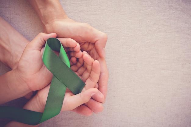 Взрослая и детская руки держат зеленую ленту, осведомленность рака