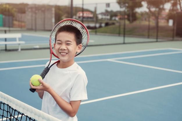 屋外の青いコートで若いトゥイーンアジア少年テニス選手