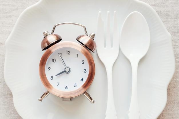 プレート上の時計、断続的な空腹時の食事療法の概念
