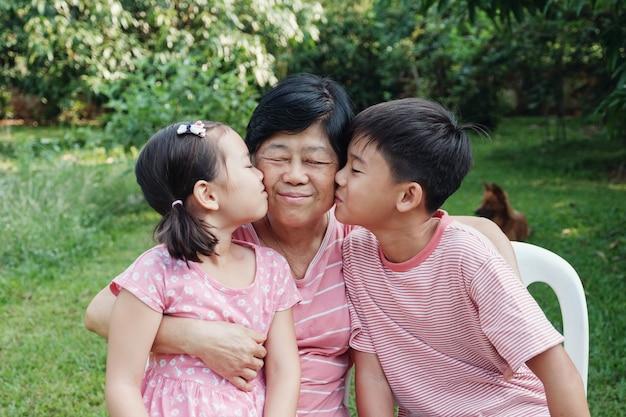 Азиатские внуки целуя их бабушку в парке, счастливую азиатскую старшую женщину