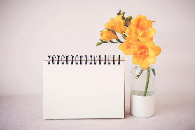 モックアップの花瓶に黄色の花とメモ帳