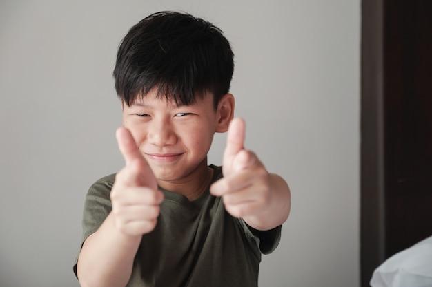 Усмехаясь азиатский мальчик подростка указывая жест оружия пальца, веселый нахальный счастливый портрет молодости