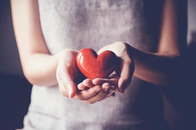 Женщина держит красное сердце, медицинское страхование, пожертвование благотворительной концепции