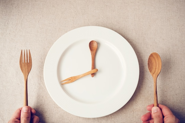 白いプレートにスプーンとフォーク、断続的な断食の概念