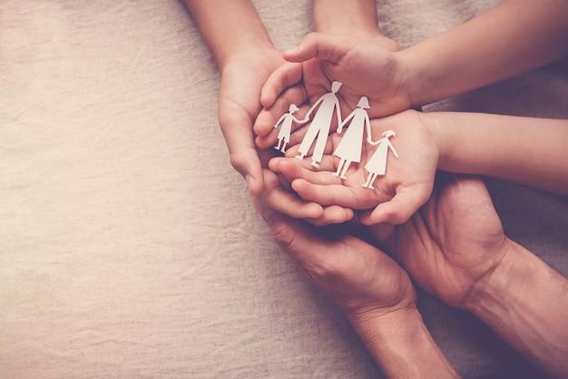 紙の家族の切り欠きを保持している大人と子供の手