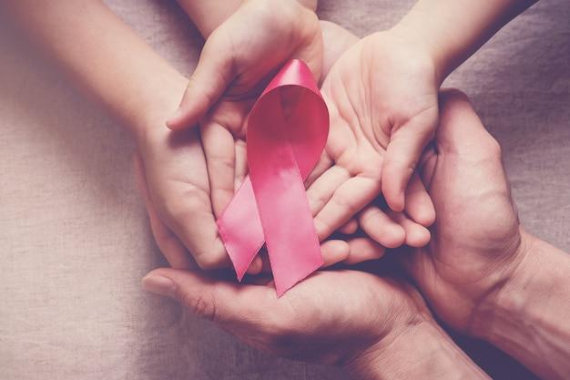ピンクのリボン、乳がんの意識を持っている家族の手
