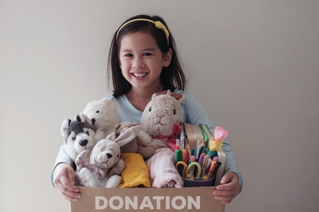 中古おもちゃでいっぱいの箱を持って混合若いボランティアの女の子