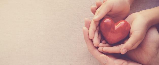 Руки взрослого и ребенка, проведение красный он, он здоровье и концепция пожертвования