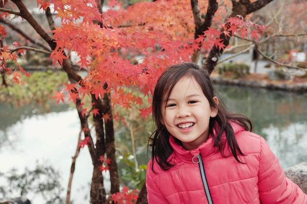 日本の赤いカエデの前で笑って幸せな小さなアジアの女の子は、京都秋のツリーを残します