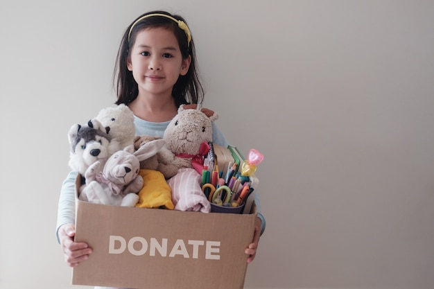 中古のおもちゃ、布、本、寄付のための文房具がいっぱい入った箱を抱えたアジアの若いボランティアの女の子