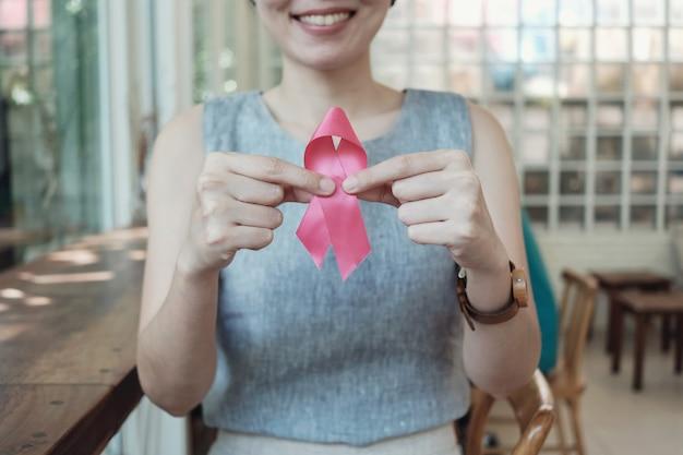 ピンクのリボン、乳がんの意識を保持しているアジアの女性