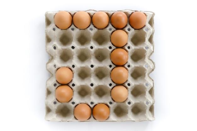 Буквы алфавита укладываются из яиц в лоток для бумаги на белом фоне.