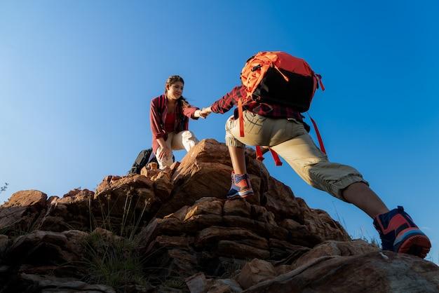 日没時の山の上のバックパックと一緒に歩いているハイカー。旅行者がキャンプに行く