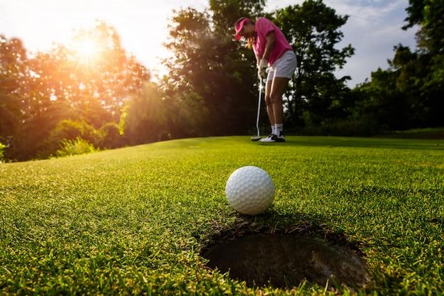 ゴルファーフォーカス砂時計、健康とライフスタイルの概念の間に穴にゴルフボールを入れて。