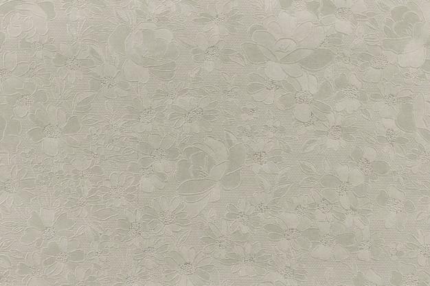 シルバーの花柄の錦織の織物のパターン。金色の背景のテクスチャ。デザインの要素。