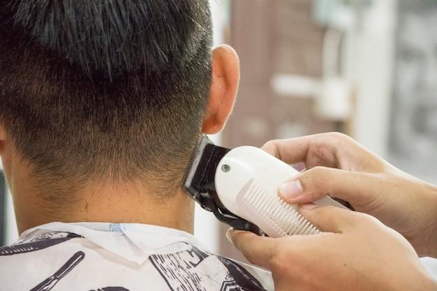 ヘアカット男性用理髪店。メンズヘアドライヤー;理髪師。理髪師は、クライアントマシンをヘアカットする。