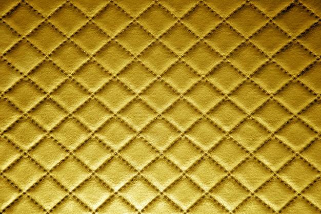 縫い目の背景を持つ金の革の質感