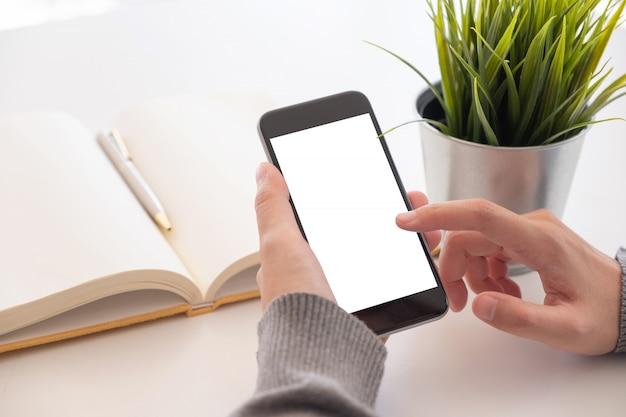 空白の画面を持つスマートフォンを使用して自宅で女性の手を閉じる。