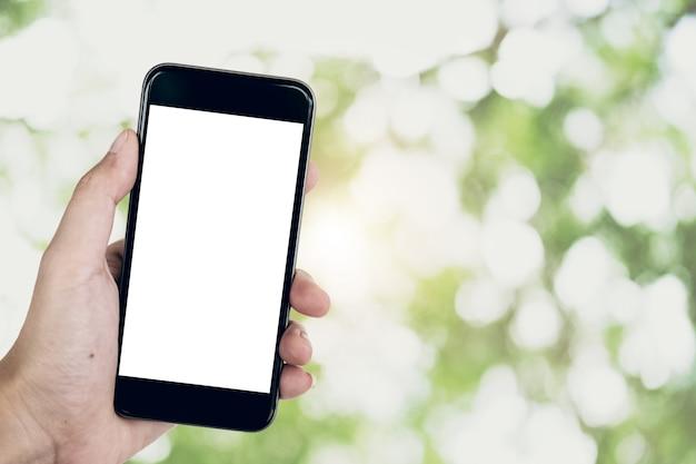 空白の画面を持つスマートフォンを使用して女性の手を閉じます。