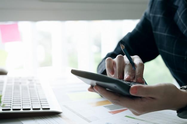 電卓に取り組んでいる鉛筆を持っているビジネスマンや会計士の手のクローズアップ