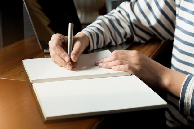 Бизнес-леди используя компьютер во время примечания некоторые данные на блокноте.