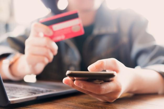 オンライン支払い、コンピューターを使用して若い男の手とオンラインショッピングのクレジットカードを持っている手。