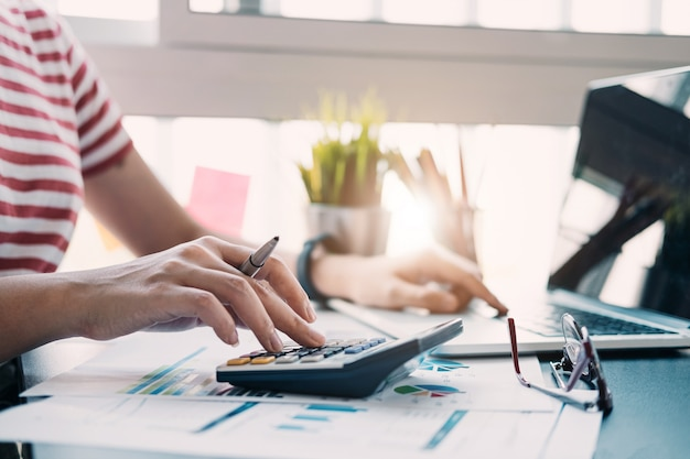 Закройте вверх по взгляду рук бухгалтера или финансового инспектора делая отчет, высчитывая или проверяя баланс. домашние финансы, инвестиции, экономика, экономия денег или страхование