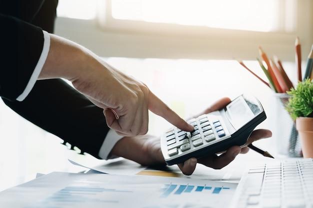 Закройте вверх бизнес-леди используя калькулятор для делает математики финансы на деревянном столе в работе офиса и концепции дела, налогов, бухгалтерии, статистики и аналитических исследований