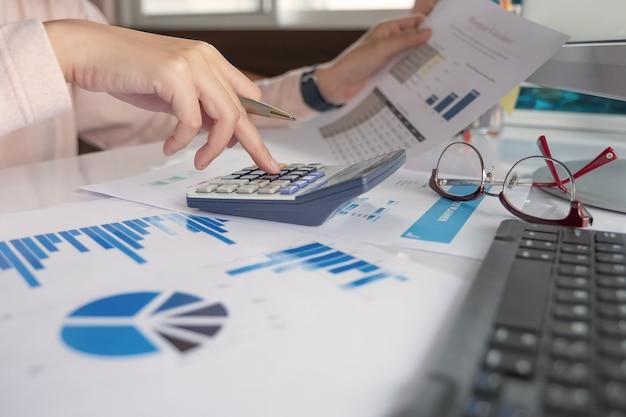 Закройте вверх по бизнес-леди используя калькулятор и компьтер-книжку для финансов математики на деревянном столе в офисе