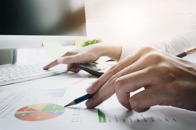Женщина используя компьютер пока работающ для финансовых документов