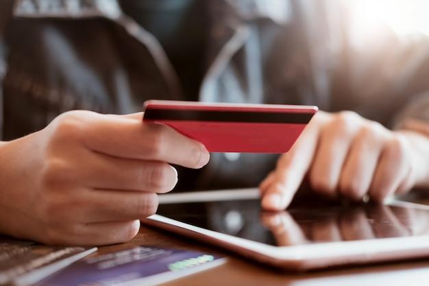 女性はカードを保持し、木製のテーブル、オンラインショッピング、クレジットカードを保持しているとラップトップを使用して手でタブレットを使用します。