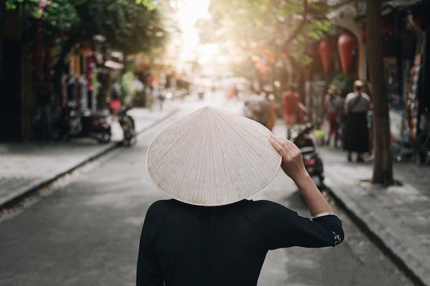 アジアの女性は休日にリラックスして旅行します。彼女の手は帽子に触れ、ダナンの旧市街の景色を見ました。