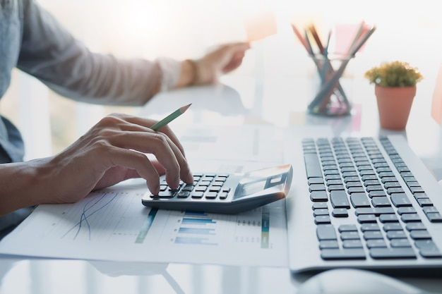 Закройте вверх руки бизнесмена или бухгалтера держа карандаш работая на калькуляторе для того чтобы вычислить отчет о финансовых данных, документ бухгалтерии и портативный компьютер в офисе, концепцию дела