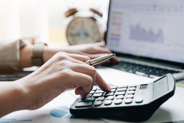 Закройте вверх по взгляду рук бухгалтера или финансового инспектора делая отчет, высчитывая или проверяя баланс.