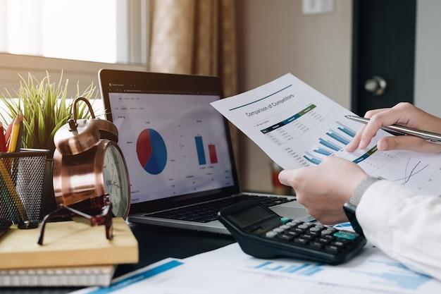 Бизнес женщина, работающая с рукой финансовых данных, используя калькулятор для анализа финансовых данных