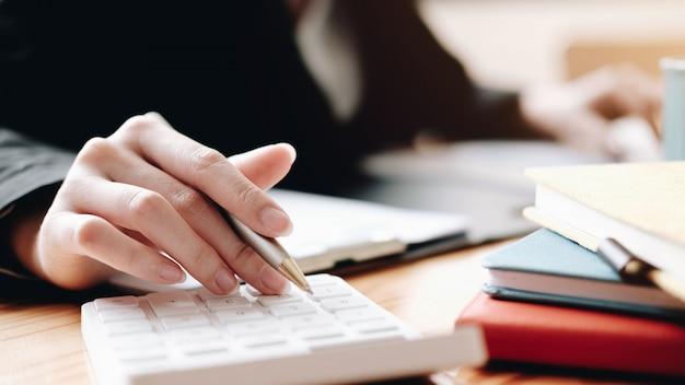 木製の机の上の計算ファイナンスを行うために電卓とラップトップを使用してビジネスの女性を閉じる