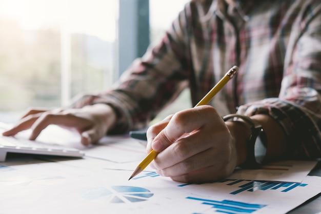 Анализ бизнесменов, обсуждая графики и графики, показывающие результаты.