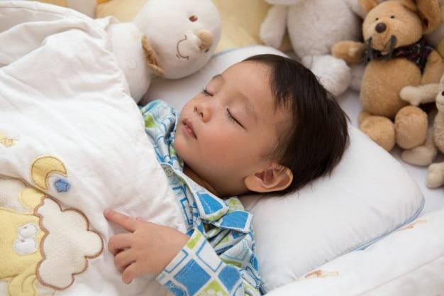 赤ちゃんは明るい部屋で寝ています。ベッドは、お金のお金のマウスの人形で飾られています。