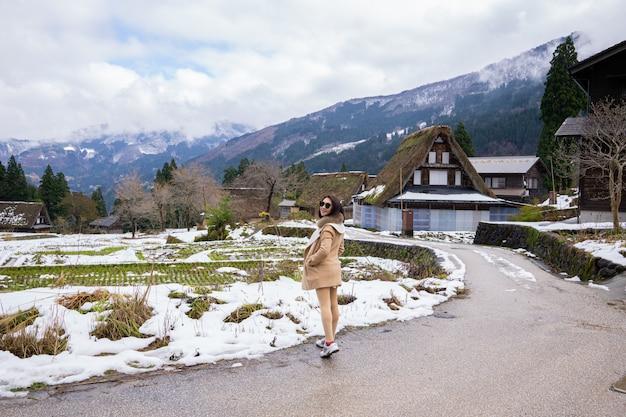 Деревня молодых женщин с деревянным домом наследия окружена японией