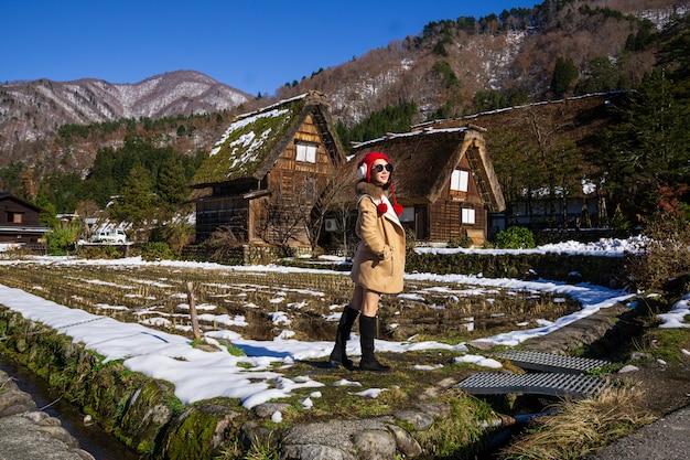 Молодая женщина в красной шапочке с наследие деревянного сельского дома фоне.