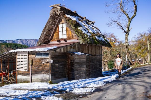 Молодые женщины стоят с деревянным домом наследия в известной деревне японии.