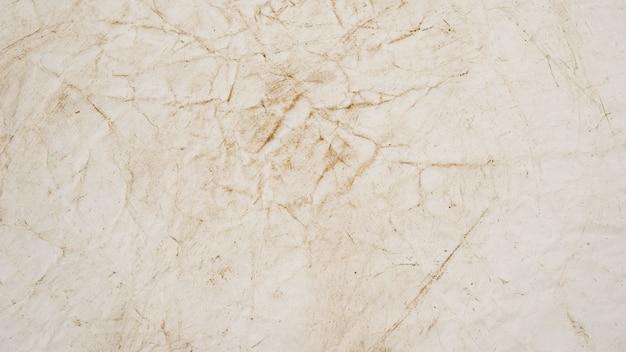 Грубая бежевая бумага гранж фоновой текстуры