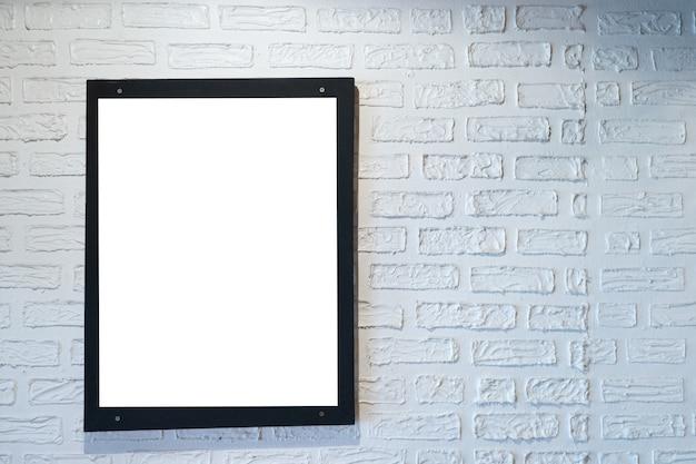 白いレンガの壁に黒いフレームのポスターの写真。