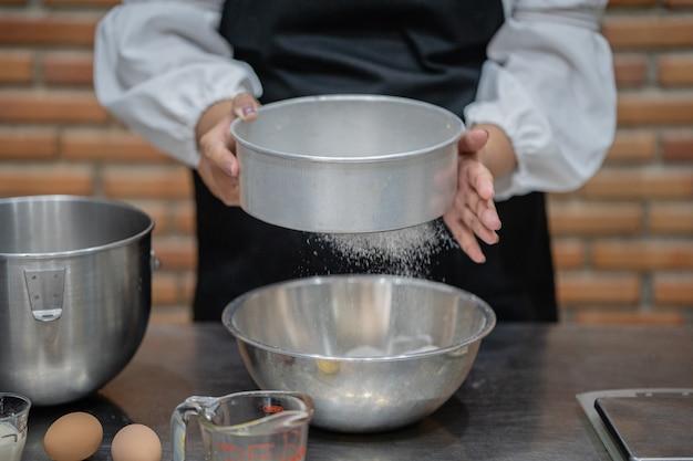 若い女性シェフが台所でケーキを調理