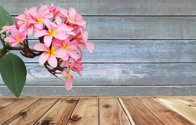 木製の床と壁の背景にプルメリアの花