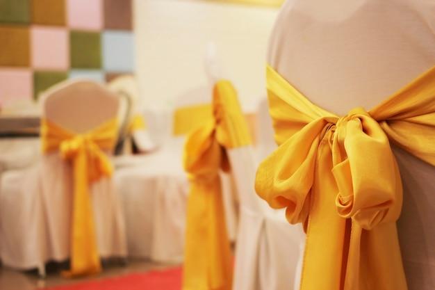 結婚式の椅子を飾るために使用されるぼやけた金色の生地。