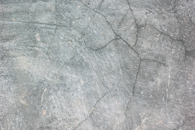 き裂を有する古い灰色のセメントの壁の表面。